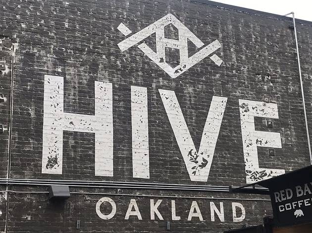 """A white sign on a black brick wall that reads """"Hive Oakland"""""""