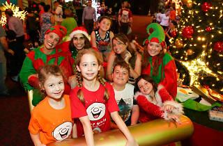 Kids and elves in a sleigh at the Santa Spectacular.