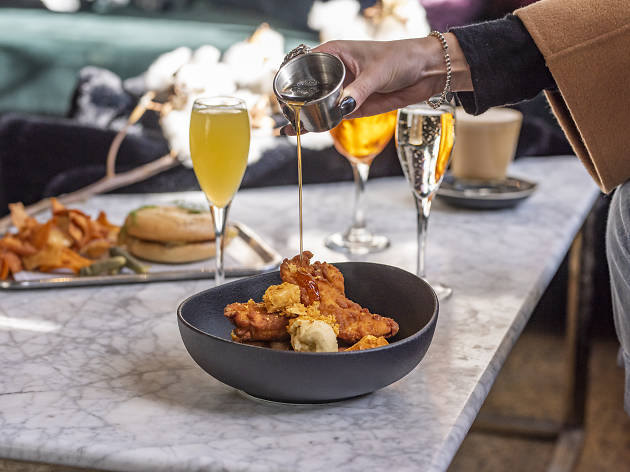 Fried chicken in a bowl with mimosas in the background