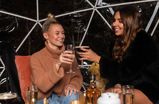 Two women cheersing glasses in a see through igloo