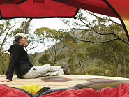 Person sitting outside a tent with bushland in the background