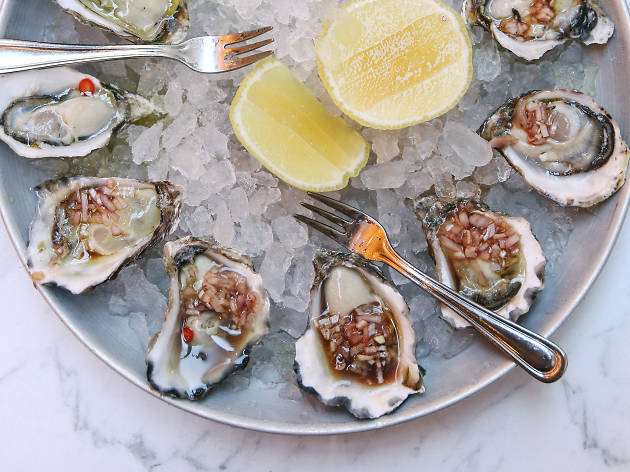Fresh oysters with vinaigrette and lemon on ice.