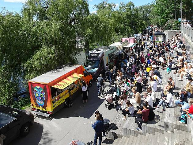 Street food vans and sunbathers at Hornstull Strand in Stockholm