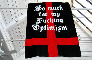 """A black flag with a red cross on it overlaid with """"So much for my Fucking Optimism"""" in white gothic font"""