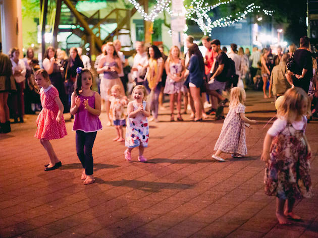 Kids and families dancing under fairy lights.
