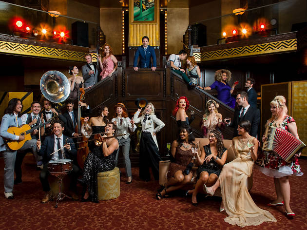 The Postmodern Jukebox crew sitting on stairs with instruments.