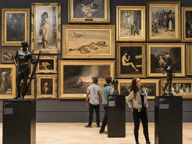 Room filled with paintings hung 'salon' style at the NGV