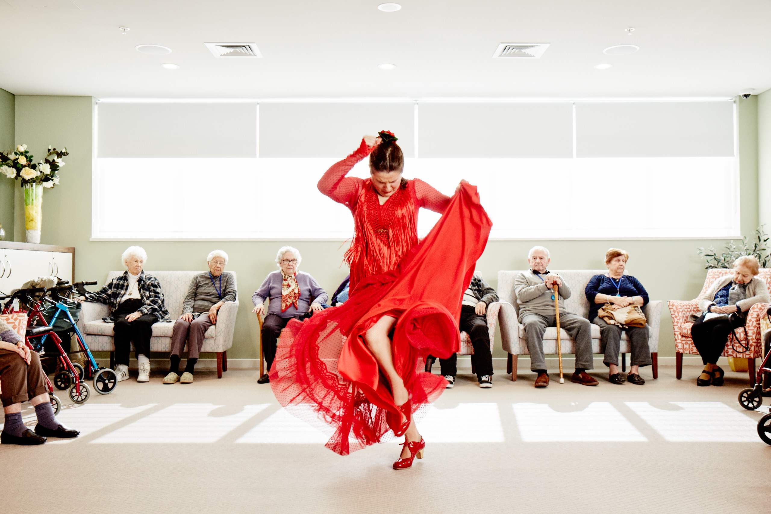 Woman in a red dress dancing in front of seated elderly people for Blacktown's Magnify festival.