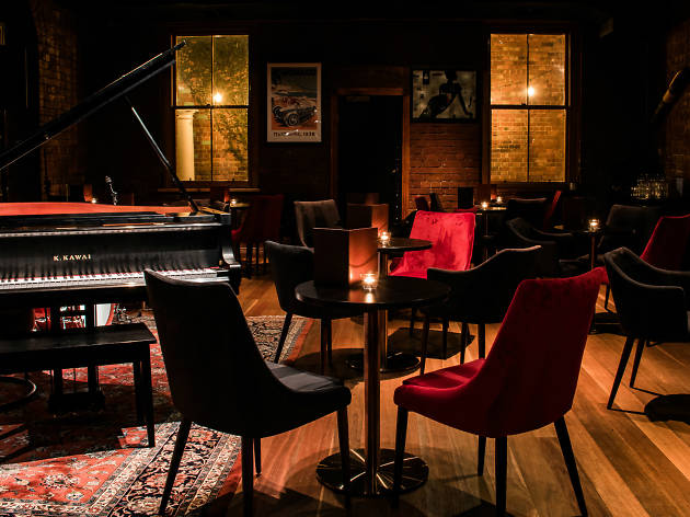 Candle-lit room with a piano and tables and chairs in it