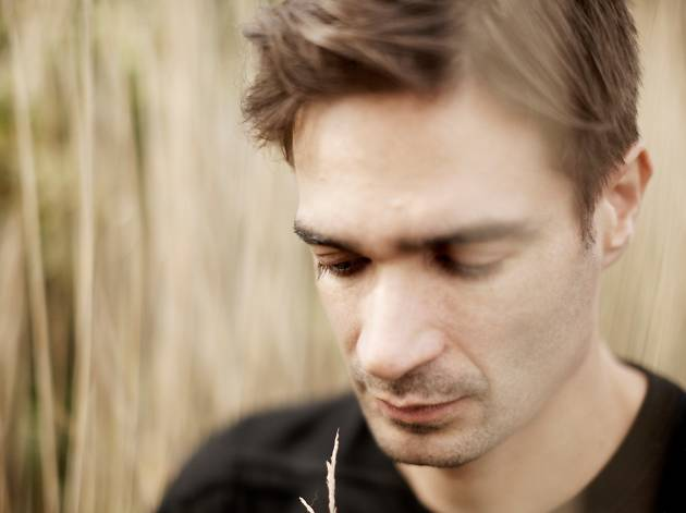 Jon Hopkins wearing a black top and looking down