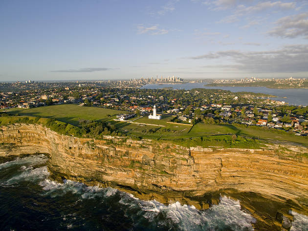 Long distance aerial shot of Macquarie Lighthouse with the city skyline in the background.