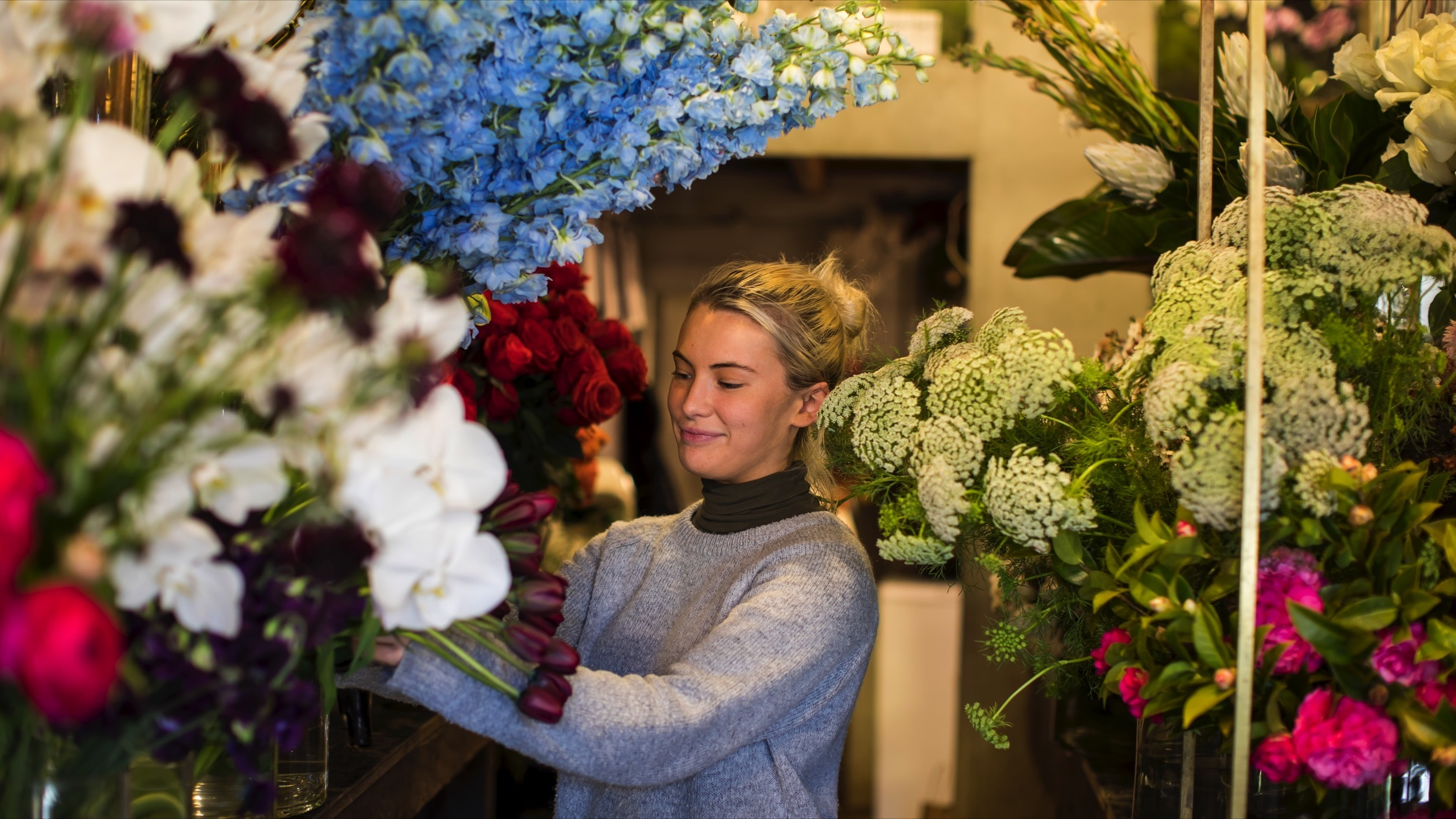 Person picking flowers at Grandiflora Florists