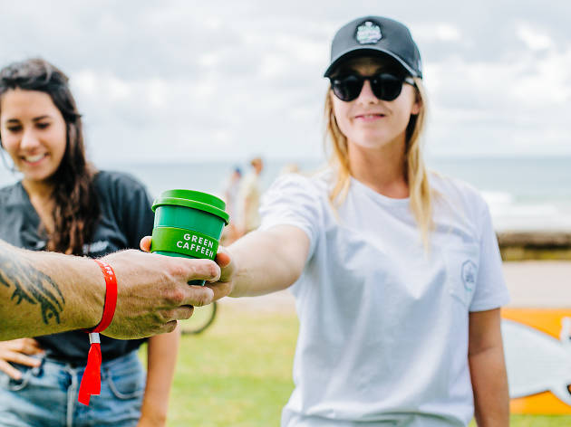 A person holding a Green Caffeen reusable takeway coffee cup.