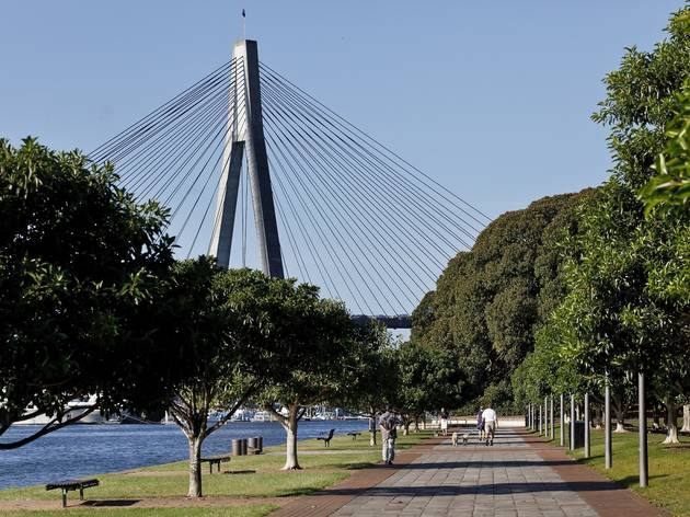 People walking along the foreshore at Blackwattle Bay Park with the ANZAC Bridge in the background