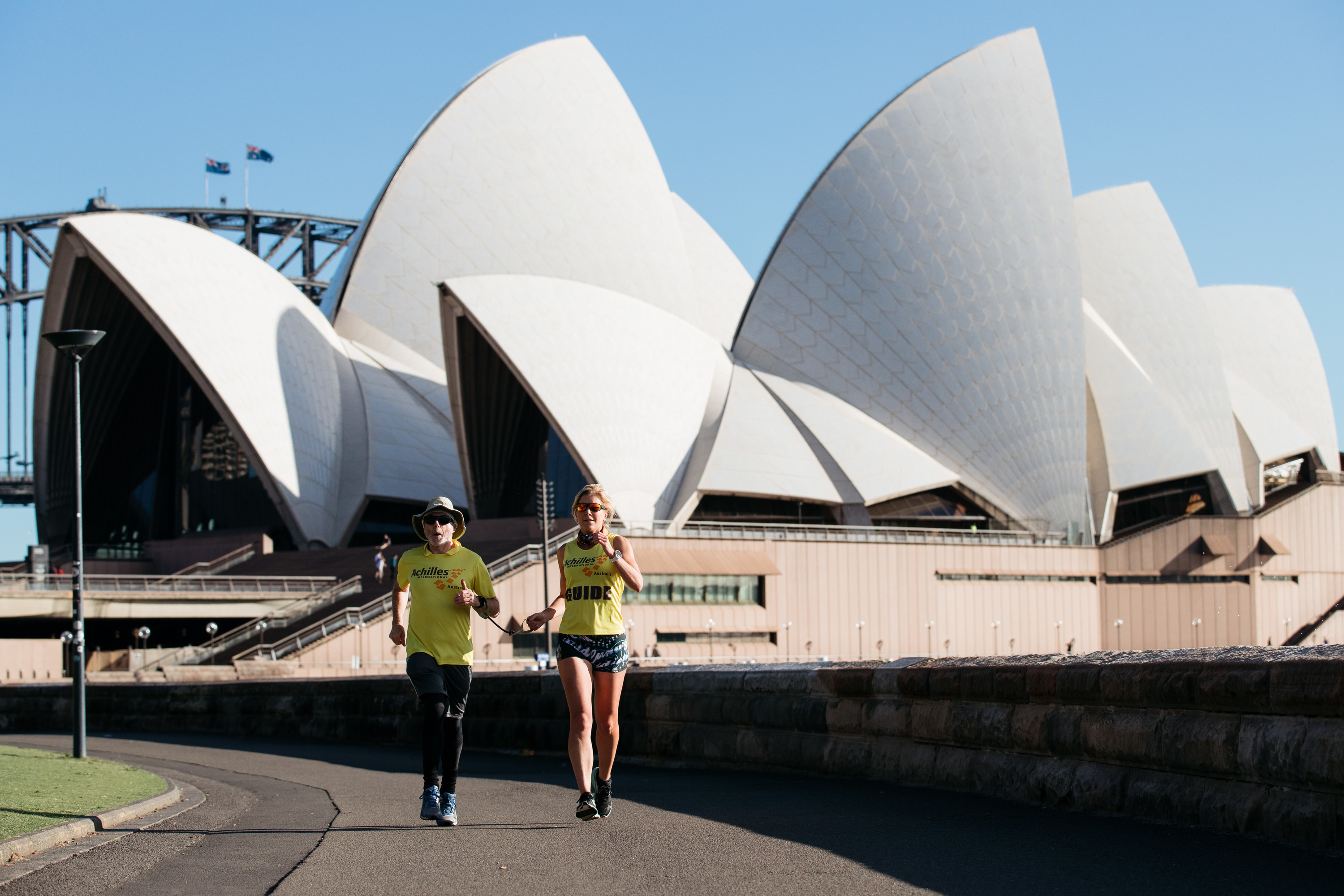 Achilles Running Club - Stephen Green and Julia Wenner running in front of Sydney Opera House