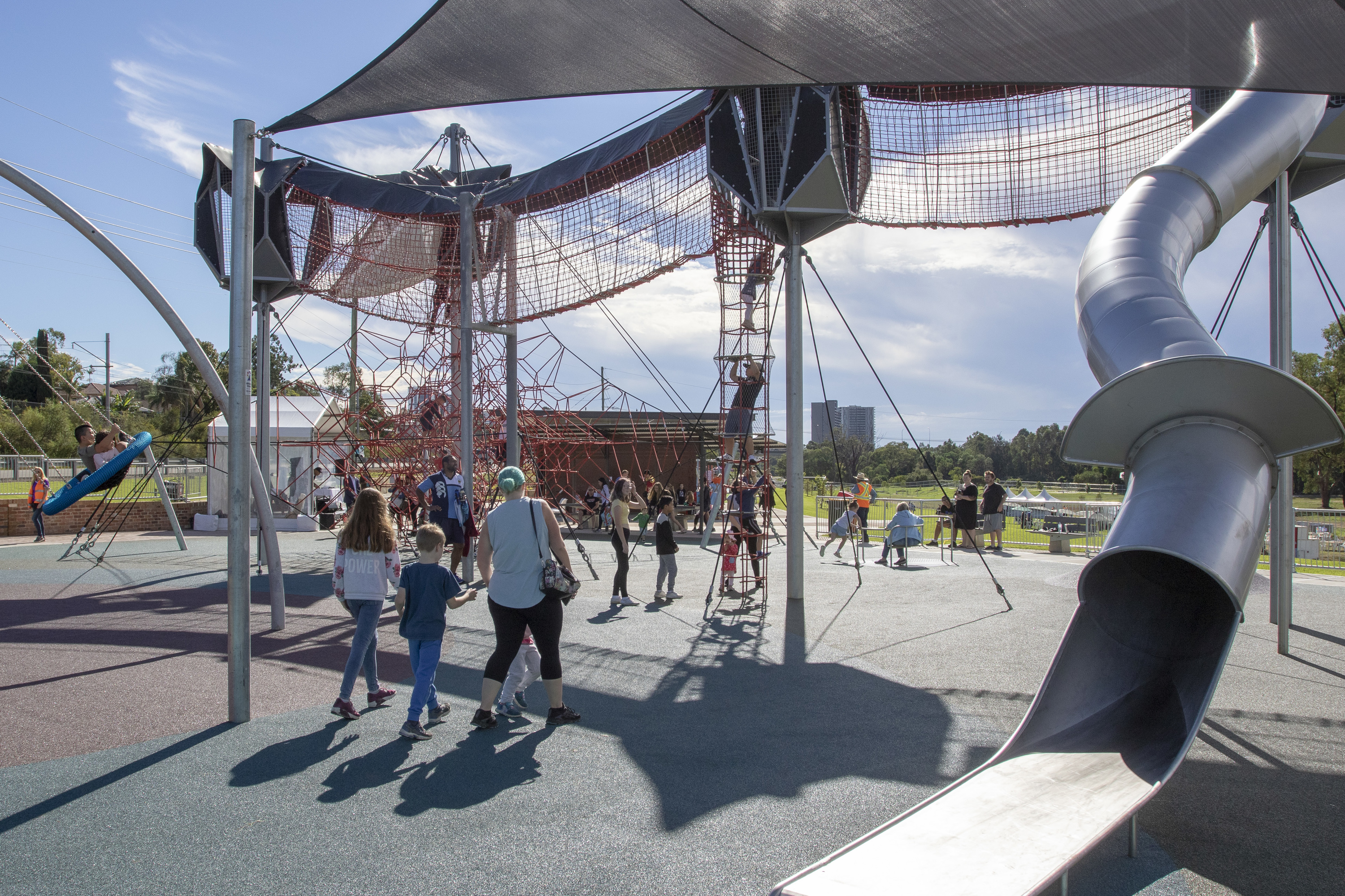 Children and adults at Casula Playground with slide, ropes and climbing net