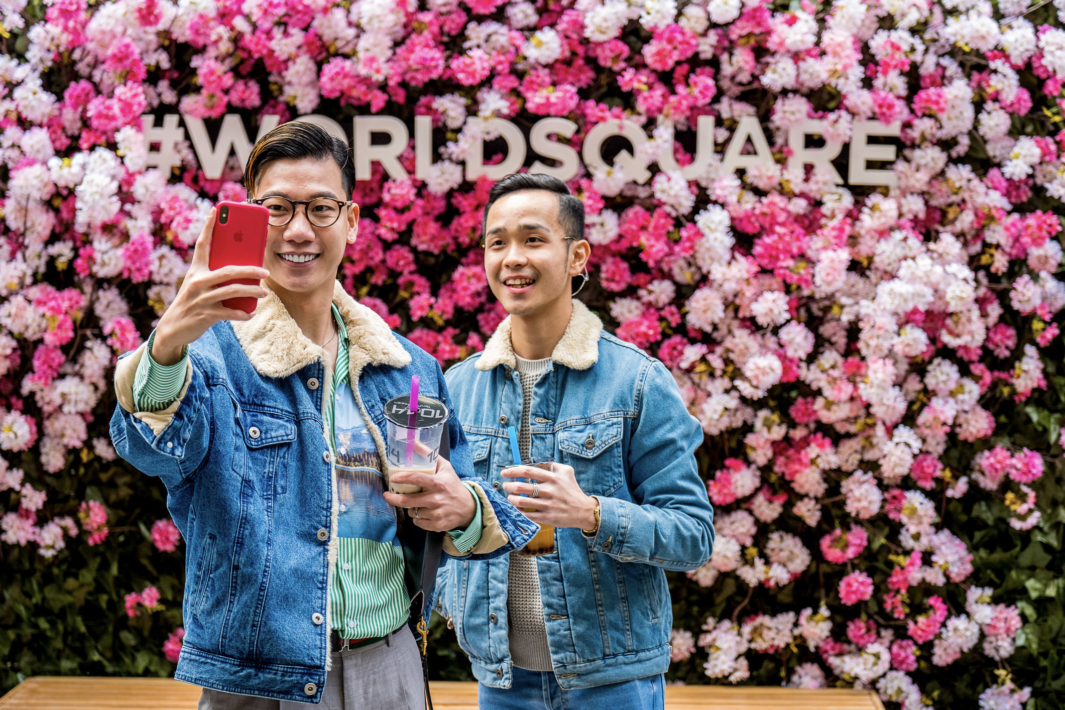 People talking selfies infront of flowers at World Square Cherry