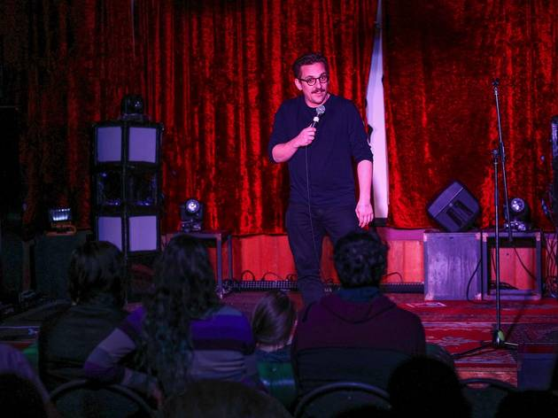Comedian on stage performing at Cat Fish Comedy Club