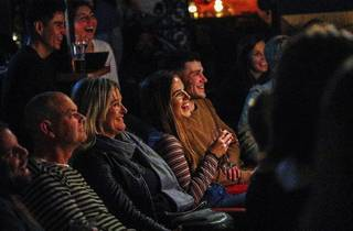 People in crowd laughing at comedy at Crab Lab