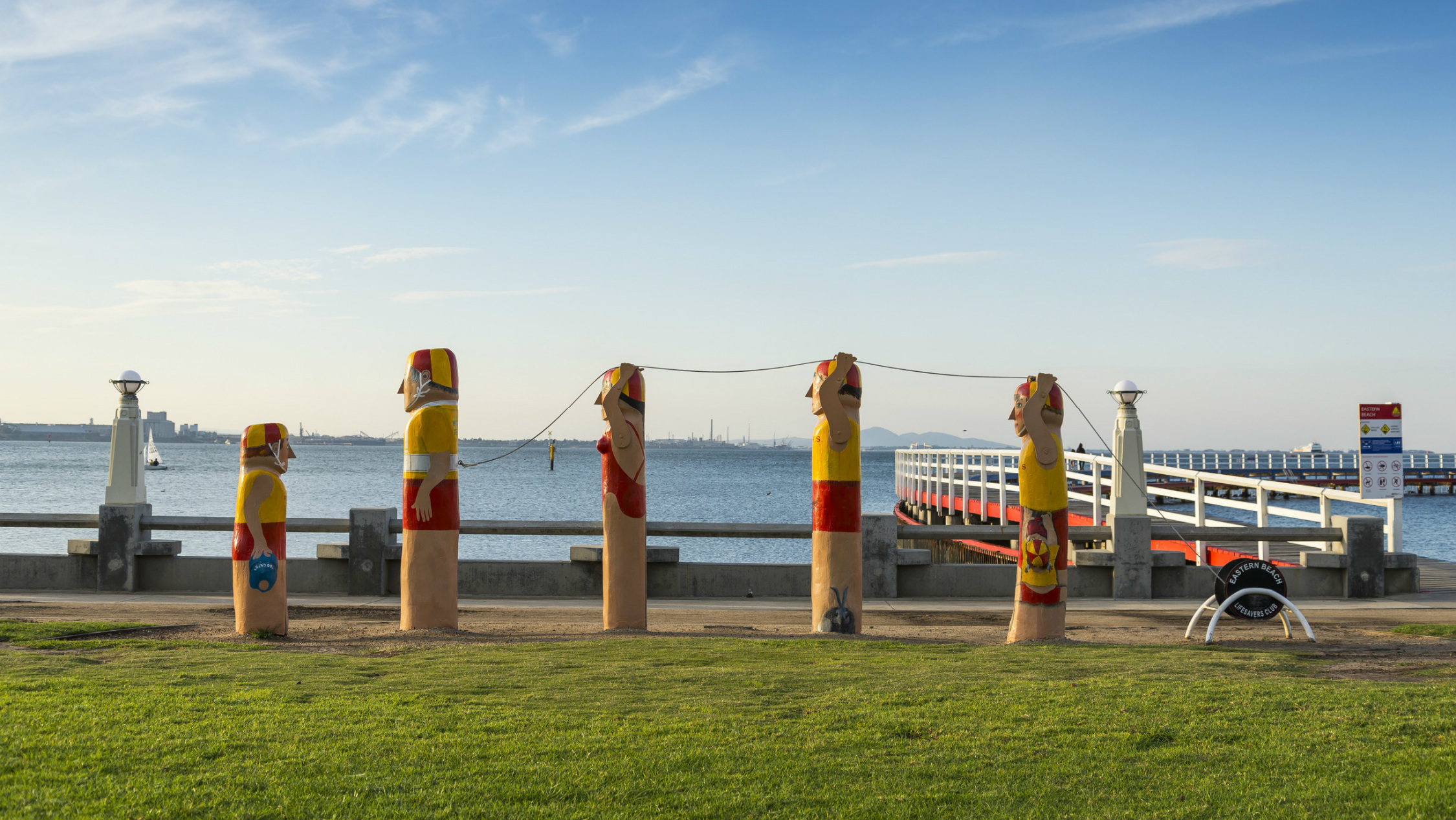 Five timber bollards painted to look like lifesavers on a lawn