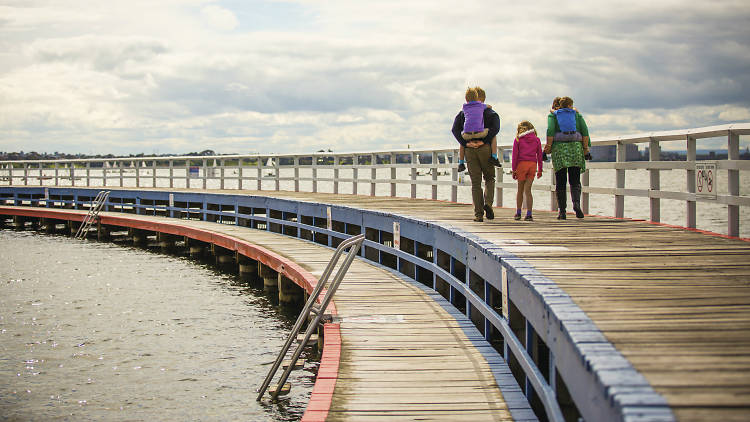 Family walking along boardwalk at Eastern Beach Reserve