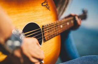 An acoustic guitar with a woman's hands playing