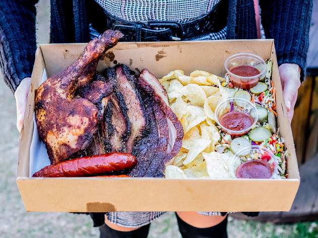 A tray of barbecue meat, chips, salad and sauce.