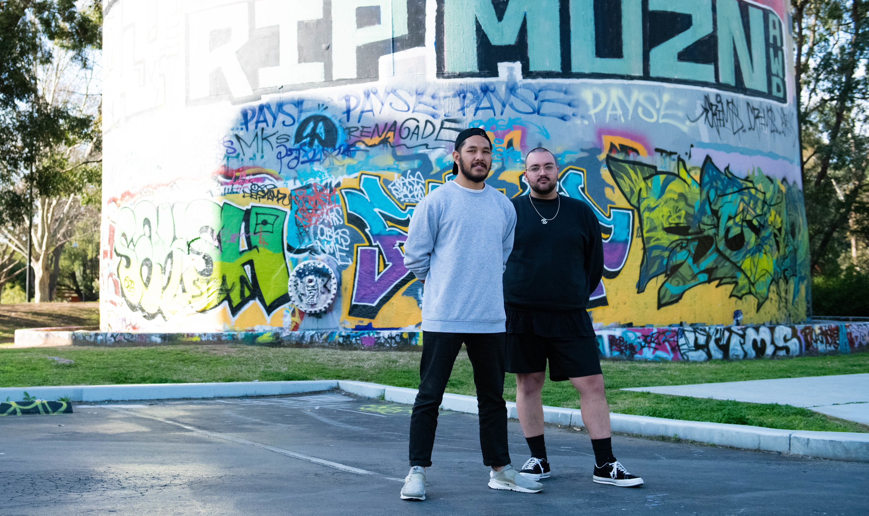 People standing in front of graffiti.