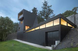 A grey building built into the side of a grassy hill.
