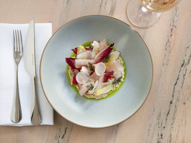 A plate of smoked swordfish with cutlery and a glass of wine at Franca