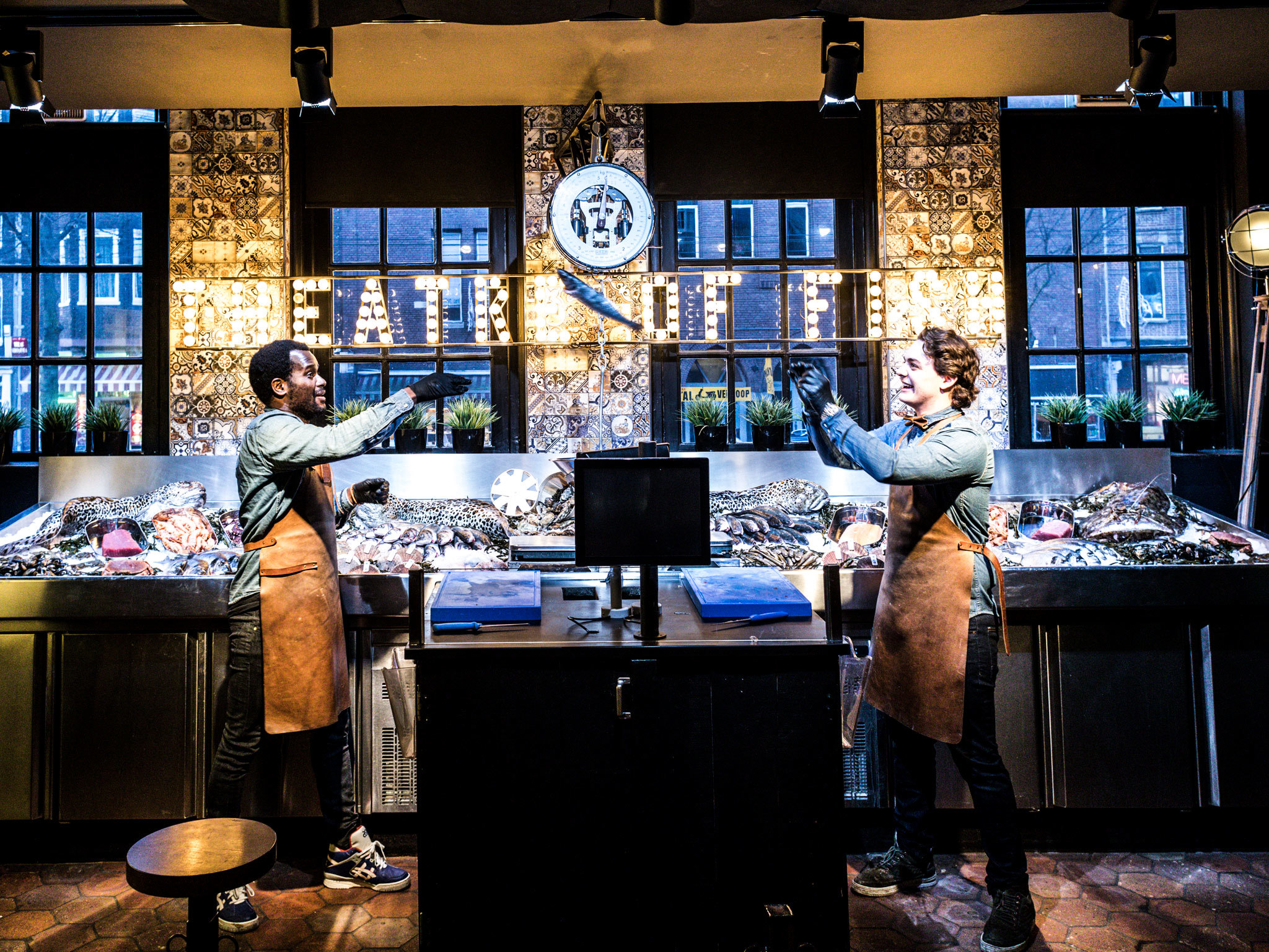 Staff throw a fish at Pesca restaurant in Amsterdam