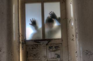 A scary image of an old door with shadows.