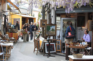 Customers and an antiques dealer at flea market the Marcheé aux Puces de St-Ouen
