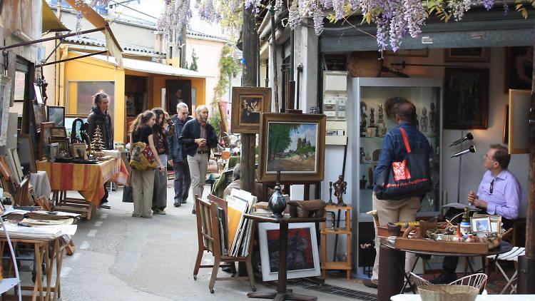 Customers and an antiques dealer at flea market the Marcheé aux Puces de St-Ouen
