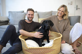 Couple sits in their living room with Guide Dog puppy, Mac.