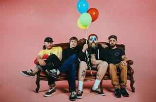Wollongong band Totally Unicorn sitting on a lounge with balloons and a pink background.