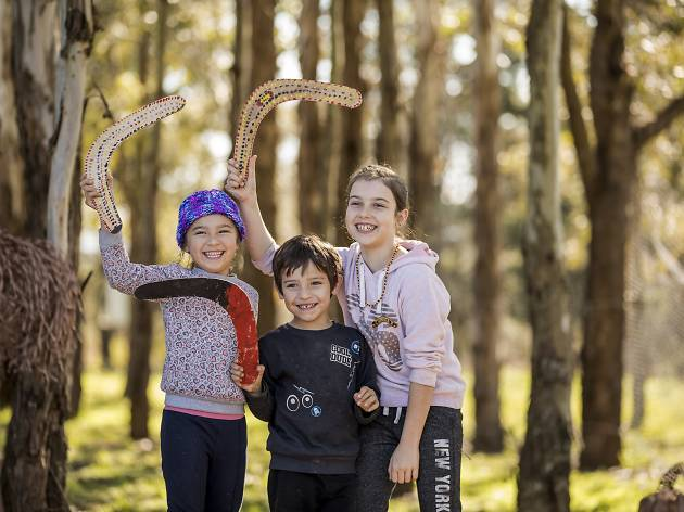 Kids with boomerangs in the bush at Rouse Hill House and Farm.