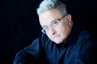 Randy Newman headshot on black background.