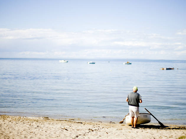 Man standing next to rowboat on the seashore