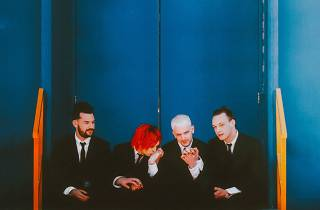 Four men sitting in suits – the 1975 indie-rock band