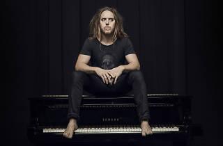 Press shot of Tim Minchin sitting on a piano