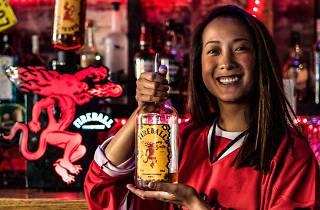 Woman holding a bottle of Fireball Cinnamon Whisky behind a bar.