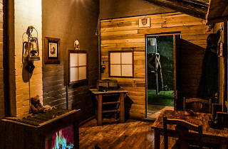 The Forgotten Son escape room interior, with a fire, tables and chairs in a shack.
