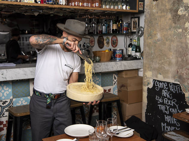 Staff member tossing cacio e pepe pasta in a wheel of cheese at Buffalo Dining Club