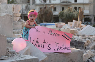 A small child holds a sing reading 'This is Aleppo - What's Justice' while standing in a crumbling building.
