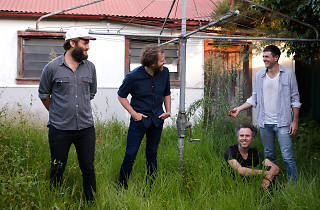 Members of band Youth Group standing in an overgrown garden with a Hills Hoist