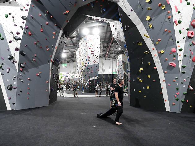 People walking through a rock climbing gym.