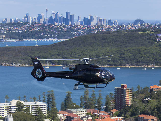 A helicopter from Sydney HeliTours flying with the city skyline in the background.