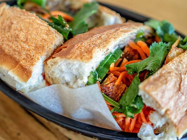 Pork banh mi sliced in half in a black basket at Yellow Fever in Redfern