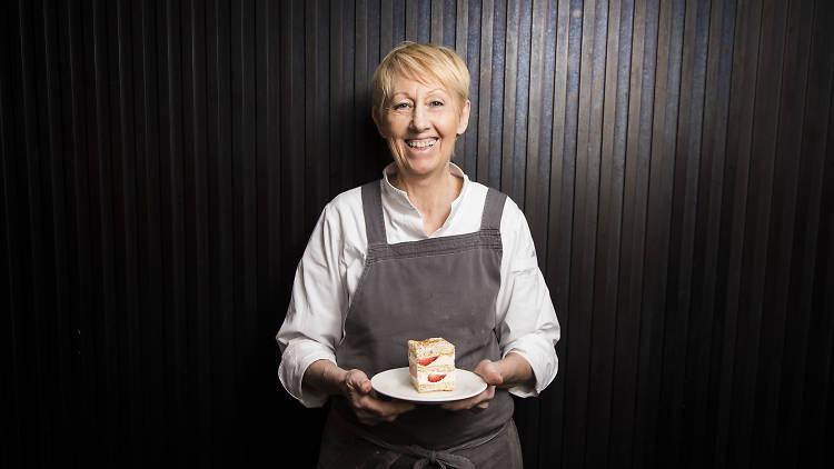 Lorraine Godsmark holding a cake outside Lorraine's Patisserie